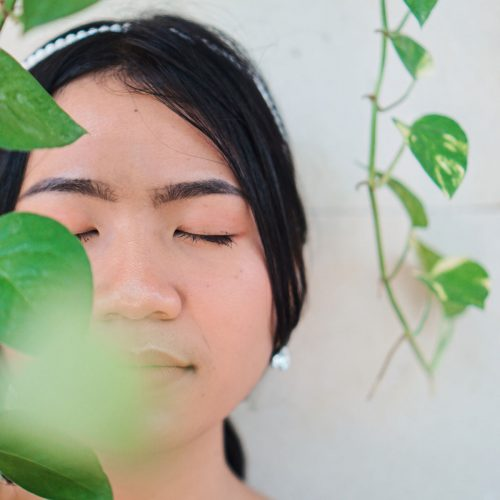 young woman with eyes closed behind vines